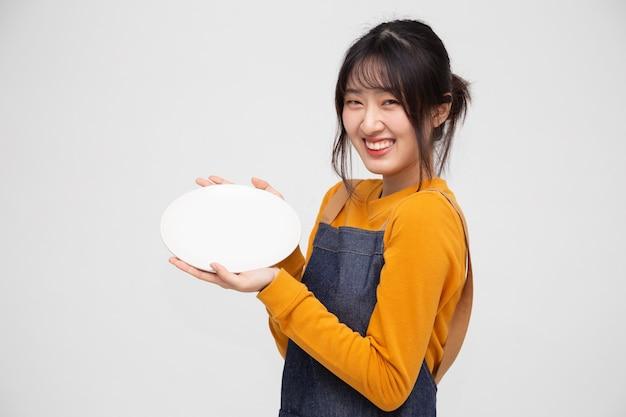 Молодая азиатская женщина в фартуке стоит и держит пустую белую тарелку или блюдо, изолированные на белом фоне