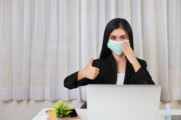 Молодая азиатская женщина в черном костюме защищает маску для здравоохранения и показывает палец вверх и сидит в офисе и работает на ноутбуке и смартфоне компьютера