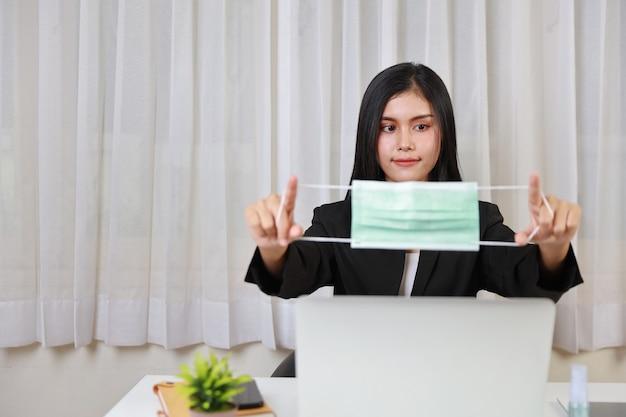 黒いスーツを着た若いアジア人女性は、オフィスでコンピューターのラップトップとスマートフォンに座って作業しているヘルスケアのためのマスクを保護します。新しい通常および社会的距離の概念