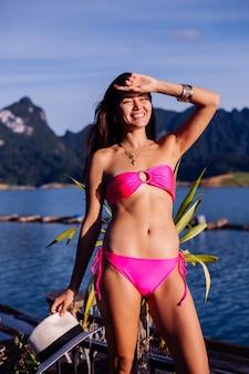 Молодая азиатская женщина в ярко-розовом бикини на отдыхе в таиланде