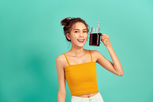 青の上に炭酸飲料を保持しているカジュアルな服を着た若いアジアの女性