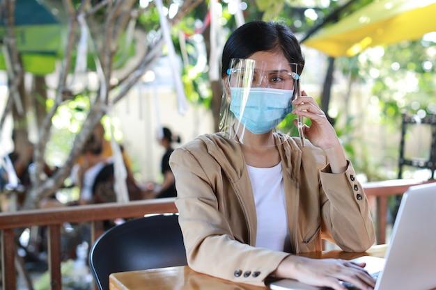 Молодая азиатская женщина в повседневном платье с маской для лица и защитной маской для здравоохранения