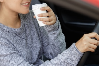 Young asian woman in casual wear driving a car and drinking coffee.