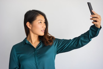 Young Asian woman in casual wear taking selfie with phone.
