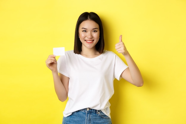 Молодая азиатская женщина в повседневной белой футболке, показывающая пластиковую кредитную карту и большой палец вверх жест, одобряет и рекомендует, улыбаясь в камеру, желтый фон.