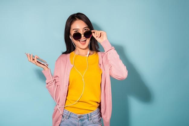 음악을 듣고 춤을 이어폰에서 젊은 아시아 여성