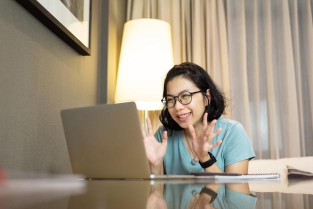 自宅のラップトップで家族とオンラインでビデオチャットを持つメガネの若いアジア女性