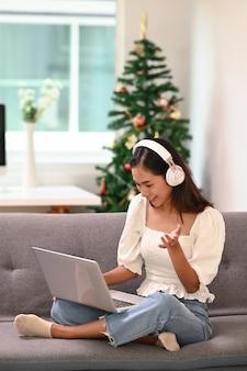 Молодая азиатская женщина в наушниках, используя ноутбук и имея видеоконференцию, сидя на диване у себя дома.