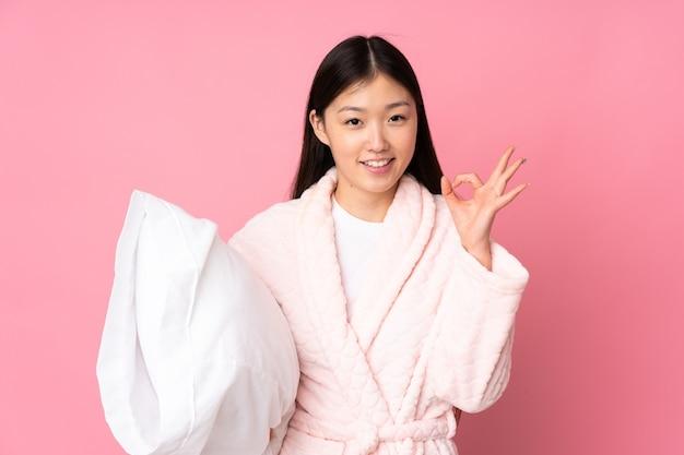 Молодая азиатская женщина в пижаме изолирована, показывая знак ок пальцами