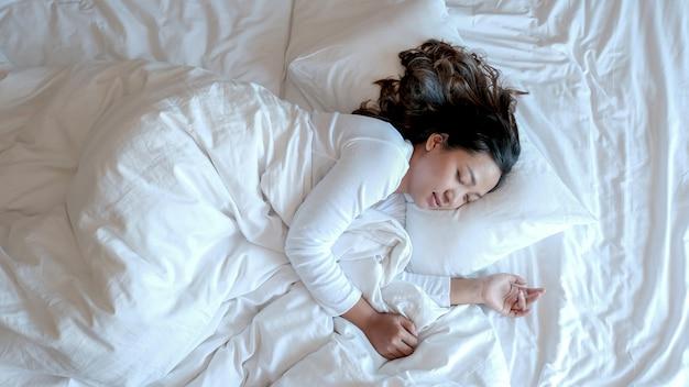 豪華な白いベッドの上に無地のtシャツを着た若いアジアの女性。