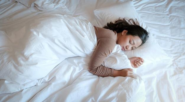 고급스러운 흰색 침대에 일반 티셔츠에 젊은 아시아 여자.