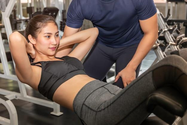 スポーツウェアトレーニングの若いアジア女性は、フィットネスジムで男性トレーナーと座ります。