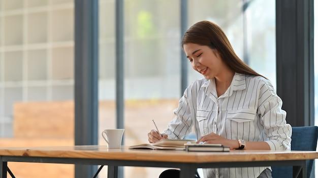 木製の作業机に座っている間ストライプシャツの執筆/メモを取る若いアジア女性。