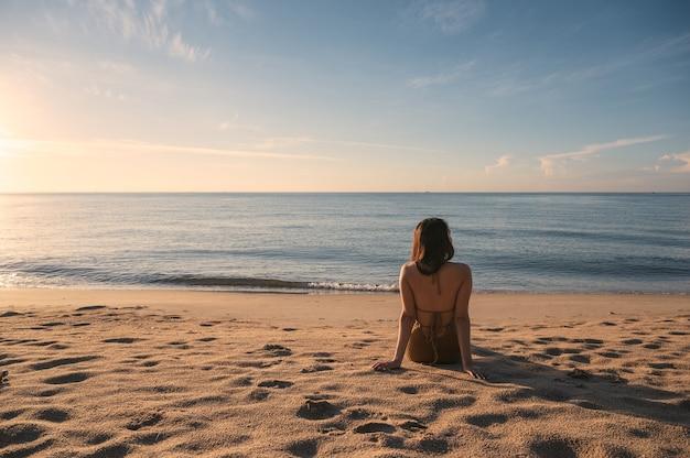 朝の太陽の光を浴びてビーチでリラックスして日光浴をする水着の若いアジア女性