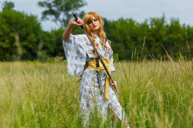 Молодая азиатская женщина в традиционном кимоно тренирует боевые приемы с мечом катана на открытом воздухе, девушка-самурай
