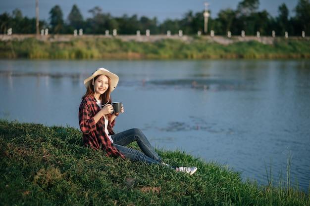 Молодая азиатская женщина в треккинговой шляпе сидит возле озера и держит кружку кофе, улыбка расслабляется во время похода