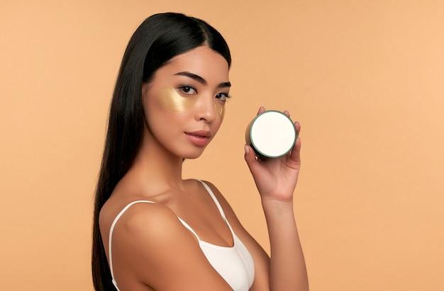 Молодая азиатская женщина в белом белье и чистой сияющей коже с увлажняющими пятнами под глазами на бежевом