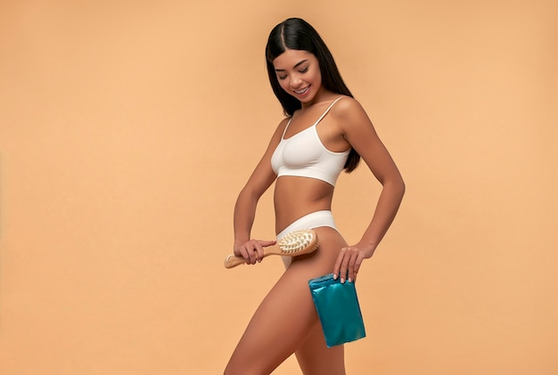 白いランジェリーの若いアジアの女性はベージュの乾いたブラシでアンチセルライトマッサージを行います