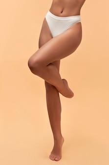 Молодая азиатская женщина в белом белье с подтянутым телом и стройной фигурой на бежевом. лазерное удаление волос. пластическая хирургия