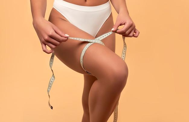 Молодая азиатская женщина в белом белье с подтянутым телом и стройной фигурой с рулеткой на бежевом. спорт, здоровый образ жизни