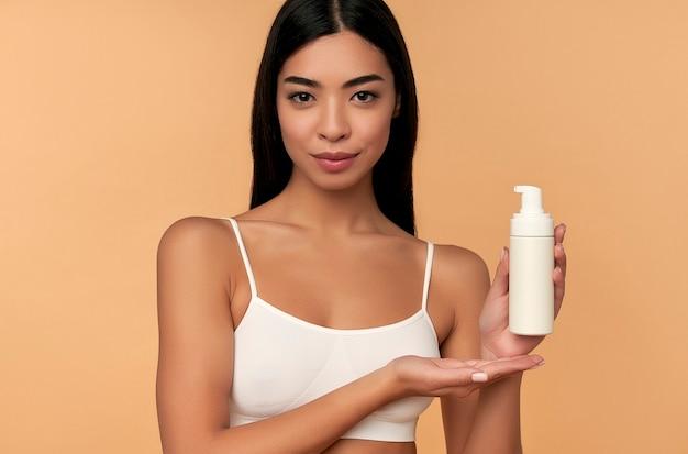 ベージュに分離された顔の泡のボトルで肌を輝く白いランジェリーの若いアジア女性