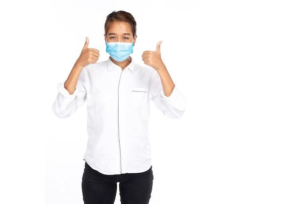 Молодая азиатская женщина в белой рубашке носит маску и показывает палец вверх двумя руками