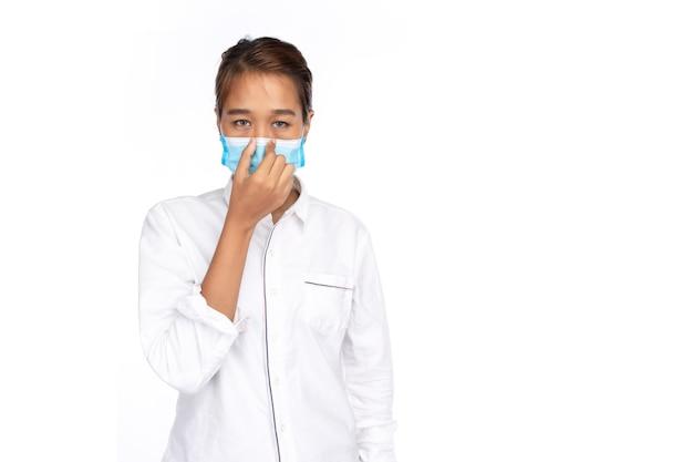 Молодая азиатская женщина в белой рубашке носит маску для лица, касается ее носа и смотрит в камеру