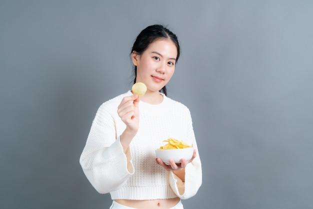 회색 벽에 감자 칩을 먹는 흰색 스웨터에 젊은 아시아 여자