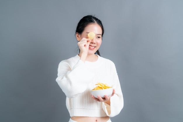 Молодая азиатская женщина в белом свитере ест картофельные чипсы на сером фоне