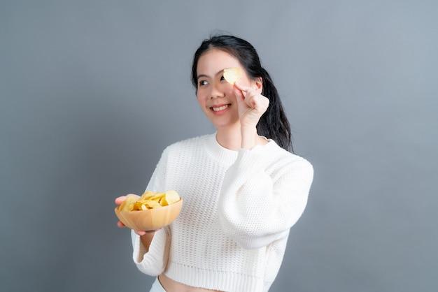 회색 벽에 감자 칩을 eatting 흰색 스웨터에 젊은 아시아 여자