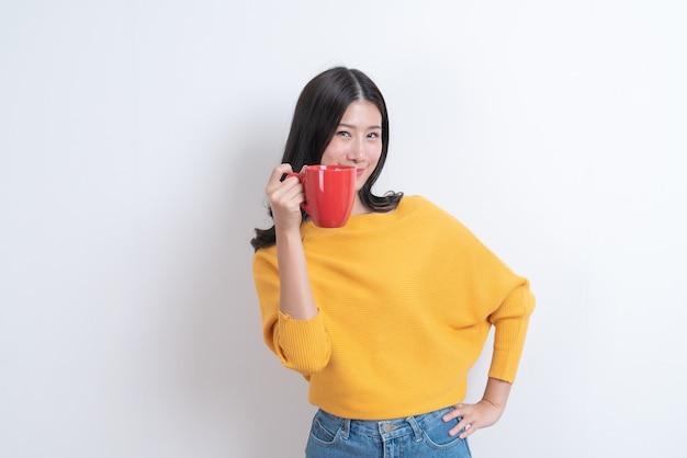 一杯のコーヒーを保持している黄色いセーターの若いアジアの女性
