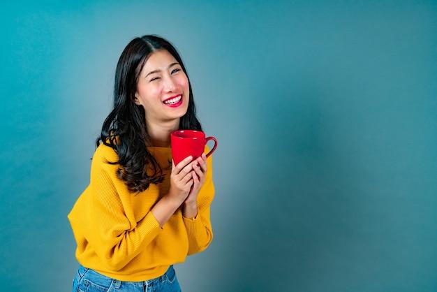 コーヒーの赤いカップを保持している黄色いセーターの若いアジア女性、良いにおいがし、ブルーのコーヒーを楽しむ