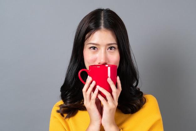 コーヒーの赤いカップを保持している黄色いセーターの若いアジア女性、良いにおいがし、灰色のコーヒーを楽しむ