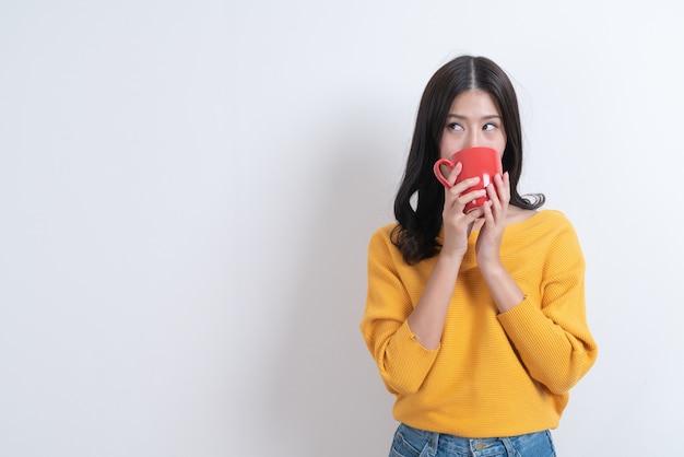 빨간 커피 잔을 들고 노란색 스웨터에 젊은 아시아 여자, 좋은 냄새와 화이트 커피를 즐길 수