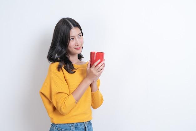 コーヒーの赤いカップを保持している黄色いセーターの若いアジア女性、良いにおいがし、白でコーヒーを楽しむ