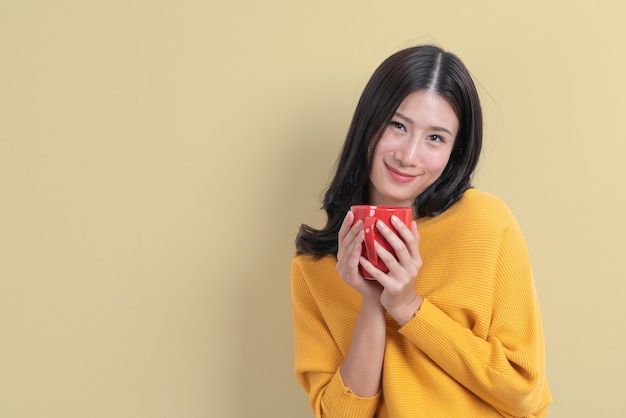赤いカップのコーヒーを保持している黄色いセーターの若いアジア女性、良いにおいがし、黄色のコーヒーを楽しむ