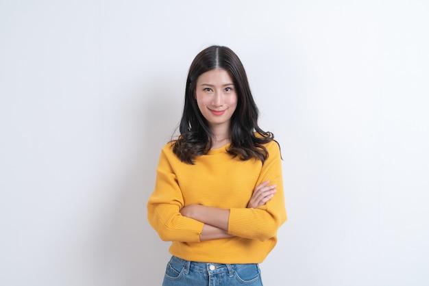 흰색에 행복 웃는 얼굴로 노란색 스웨터에 젊은 아시아 여자
