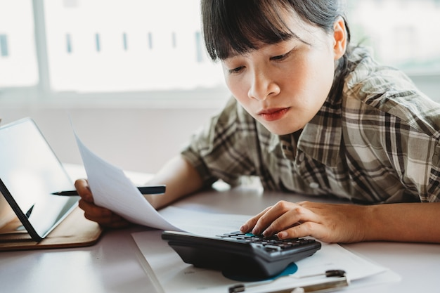 젊은 아시아 여자 지불 할 세금을 계산