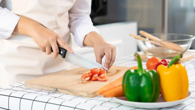 若いアジア人女性は、軽いキッチンのまな板の材料のためにトマトを切ること、家庭での料理、そして健康食品のコンセプトによって健康食品野菜サラダを準備しています。