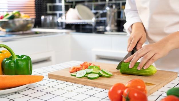 Молодая азиатская женщина готовит овощной салат здоровой пищи