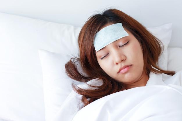 Молодая азиатская женщина больна и спит в постели.