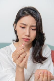 若いアジアの女性が居間で薬を服用している必要な薬をより安全に服用している薬に焦点が当てられている人々がぼやけている