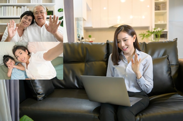 A young asian woman is using laptop computer to video calling or webcam to greeting her family ,  telecommunications technology , parenthood family concept