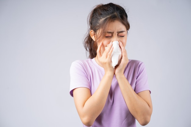 若いアジアの女性はティッシュで彼女の鼻を拭いています