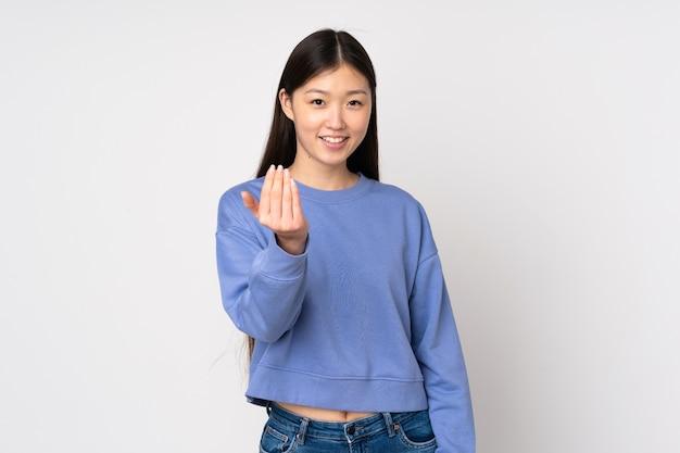 Молодая азиатская женщина, изолированных на фоне, приглашая прийти с рукой. счастлив что ты пришел