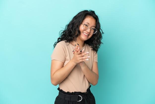 Молодая азиатская женщина изолирована на синем фоне аплодирует после презентации на конференции
