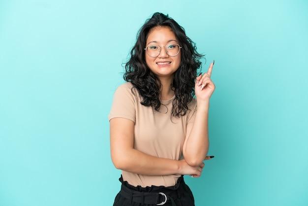 幸せで上向きの青い背景に分離された若いアジアの女性