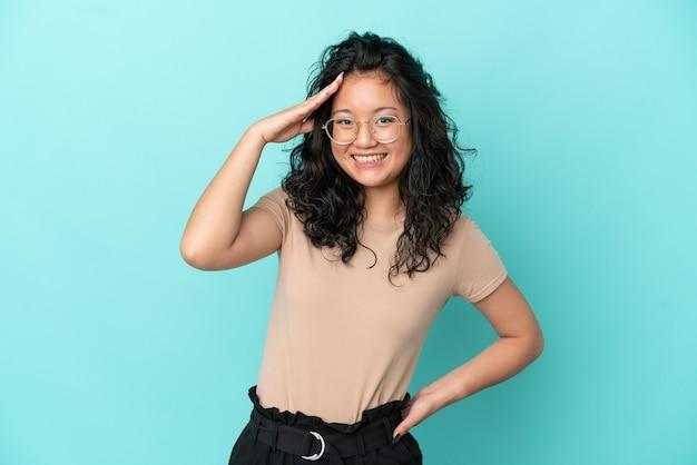青い背景で隔離の若いアジアの女性は何かを実現し、解決策を意図しています