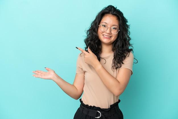 Молодая азиатская женщина изолирована на синем фоне, держа воображаемое copyspace на ладони, чтобы вставить рекламу