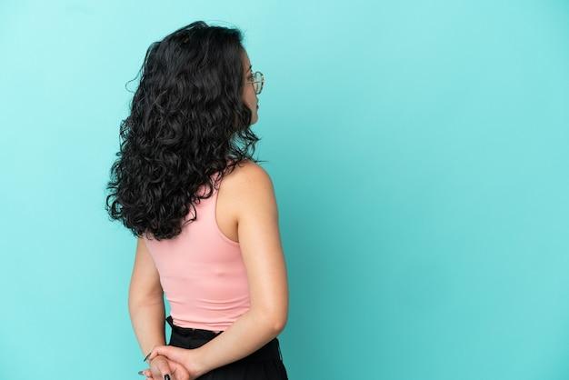 Молодая азиатская женщина изолирована на синем фоне в задней позиции и оглядывается назад
